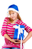 Little girl in Santa's hat with blue gift box Royalty Free Stock Photos