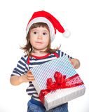 Little girl in Santa's hat with gift box Stock Photos