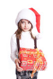Little girl with santa's hat and gift holding Stock Image