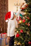 Little girl in Santa's hat putting ball on top of Christmas tree Royalty Free Stock Image