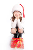 Little girl with santa's hat. Sitting near gift Royalty Free Stock Photography