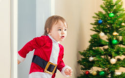 Little girl in a santa suit dashing to open her Christmas presents Stock Photo