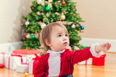 Little girl in a santa suit playing under the Christmas tree Royalty Free Stock Image