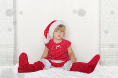 Little girl in Santa suit sitting on floor with snow Royalty Free Stock Images