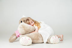 Little girl sat with cuddly toy and smile Royalty Free Stock Photo