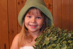 The little girl in a sauna. The smiling little girl with a broom in a sauna Stock Photo