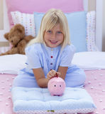 Little girl saving money in a piggy bank Royalty Free Stock Photography