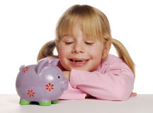 Little girl saving money with piggy bank. Stock Photos