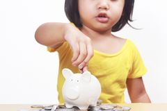 Little Girl Saving Money in Piggy Bank royalty free stock images