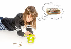 Little girl saving money in piggy bank. And wishing what to buy Stock Images