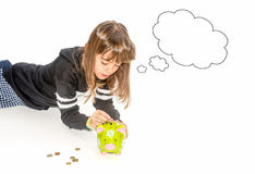Little girl saving money in piggy bank. And wishing what to buy Royalty Free Stock Photos