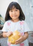 Little girl saving money in a piggybank Royalty Free Stock Photo