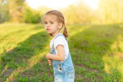 The little girl is scared, lost in the park. Summer season stock photos