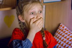 little girl is scared watching a TV Stock Image
