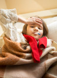 Little girl in scarf lying in bed and measuring temperature Stock Photo
