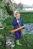 05.03.2015. A little girl in a scarf with a scythe in her hands. A child stands near a tree with an ax and smiles stock photography