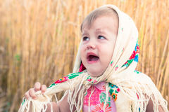Little girl in scarf stands in the middle of the field and cries. Orphans, social problems. Royalty Free Stock Photos