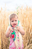 Little girl in scarf stands in the middle of the field and cries. Orphans, social problems. Stock Photo