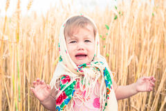 Little girl in scarf stands in the middle of the field and cries. Orphans, social problems. Royalty Free Stock Photography