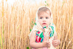 Little girl in scarf stands in the middle of the field. Royalty Free Stock Images