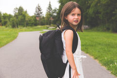 Little girl with school backpack on path looking back to camera Stock Photo