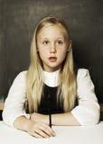 Little girl in school uniform is in classroom Royalty Free Stock Image