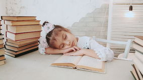 Little girl in school uniform, fell asleep while reading a book. stock video