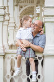 Little Girl with School Uniform and her Grandfather in Green Par Royalty Free Stock Image