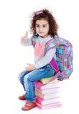 Little girl schoolgirl sitting on books Stock Photos