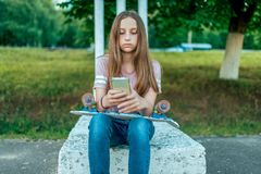 A little girl schoolgirl of 12-16 years old, sits outside in summer in street. He holds skateboard, phone, online royalty free stock image