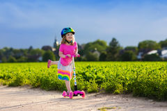 Little girl on a scooter. Little child learning to ride a scooter in a city park on sunny summer day. Cute preschooler girl in safety helmet riding a roller Stock Images
