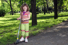 Little girl with scooter in park Royalty Free Stock Photos
