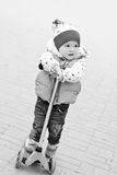 Little girl on scooter in the park Stock Photos