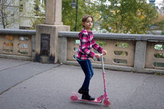Little girl on a scooter Stock Photos