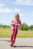 Little girl with scooters Stock Photos