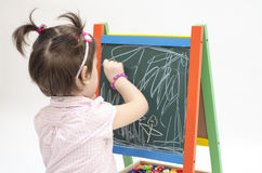 Little girl scratches with chalk on blackboard. Isolated on white background Royalty Free Stock Photos