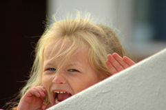 Little girl screaming. A beautiful little caucasian white girl child head portrait with angry expression in the pretty face screaming out loud while hiding and Royalty Free Stock Photography