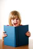 Little Girl Screaming At Her Book Stock Photo