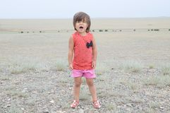 Little girl screaming in big landscape environment. Child emotionally saying loudly, singing a song with expression. Little girl screaming in big landscape royalty free stock image