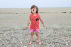 Little girl screaming in big landscape environment. Child emotionally saying loudly, singing a song with expression. Little girl screaming in big landscape royalty free stock photography