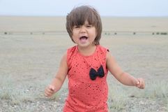 Little girl screaming in big landscape environment. Child emotionally saying loudly, singing a song with expression. Little girl screaming in big landscape royalty free stock photos