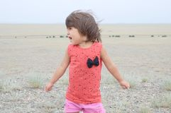 Little girl screaming in big landscape environment. Child emotionally saying loudly, singing a song with expression. Little girl screaming in big landscape stock photos