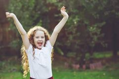Little girl raised her hands up and screaming hurray in a summer. Little girl screaming cheers, rejoicing the victory, celebration or surprise in a summer park Royalty Free Stock Images