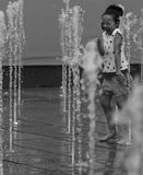 Little girl plays in water fountain jet. 07.04.2014 Bucharest, Tineretului Park. Jets of water rising from fountain while splashing a young girl and makes her stock photography