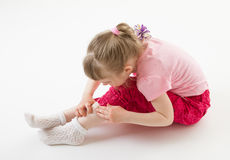 Little girl scrutinizing her leg attentively Royalty Free Stock Photos