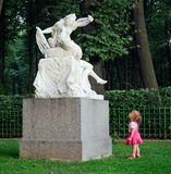 Little girl and  sculpture. The little girl with astonishment looks at a sculpture of Cupid and Psyche in old park Summer garden in St.Petersburg, Russia Royalty Free Stock Photo