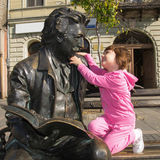 Little girl and sculpture of poet Laza Kostic royalty free stock photo