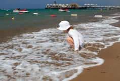 Little girl on sea beach. Stock Photos