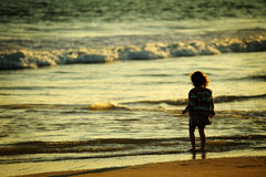 Little girl on the sea beach at sunset Stock Images