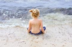 Little girl watching the ocean. Small girl sitting and watching waves Stock Photo